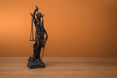 bronze statuette with scales of justice on wooden table on orange background Stok Fotoğraf