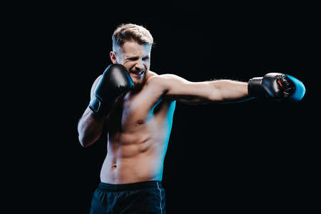 muscular sporty boxer with strenuous face expression in boxing gloves doing punch isolated on black