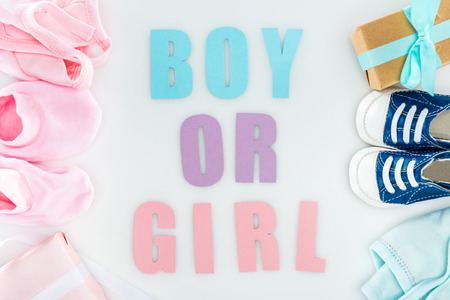 top view of booties and sneakers, boy or girl lettering, gift boxes and bonnets