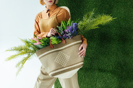 partial view of stylish young woman holding bag with fern and flowers on white with green grass