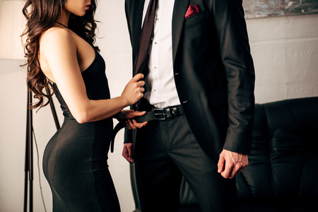 cropped view of sexy girl in black dress holding tie of man