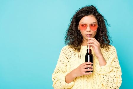 lockiges afroamerikanisches Mädchen mit Sonnenbrille, das eine Flasche mit Strohhalm hält und Soda trinkt, isoliert auf Blau Standard-Bild