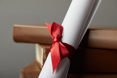 Brown books and diploma with red ribbon on grey
