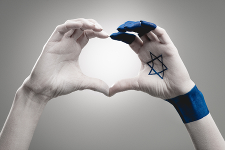 cropped view of female hands with star of david showing heart on grey Stockfoto