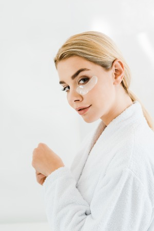 beautiful and blonde woman in white bathrobe with eye patches on face looking at camera in bathroom