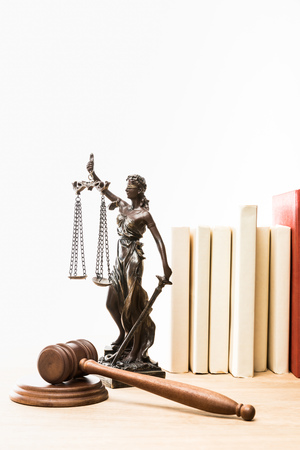 metal figure with scales of justice, gavel and books on wooden table isolated on white