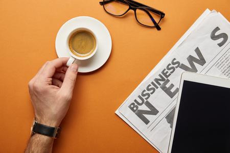 Ausgeschnittene Ansicht eines Mannes, der eine Tasse Kaffee in der Nähe eines digitalen Tablets mit leerem Bildschirm, Brille und Wirtschaftszeitung auf Orange hält Standard-Bild