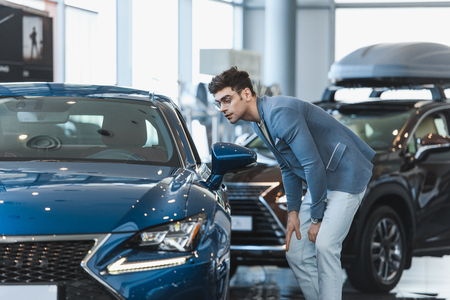 stylish man in glasses looking at automobile while standing in car showroom