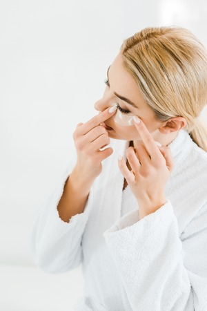 blonde and attractive woman in white bathrobe applying eye patches in bathroom Stock Photo