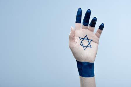 cropped view of female hand with national star of david isolated on blue 写真素材