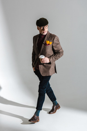 stylish middle aged man in glasses and cap walking with paper cup on grey Standard-Bild