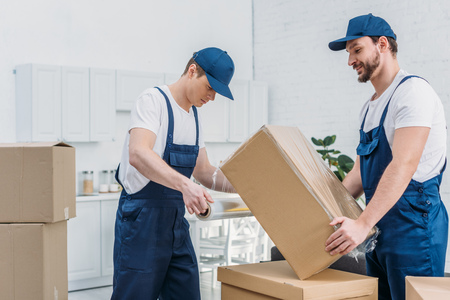 handsome movers wrapping cardboard box with stretch film in apartment