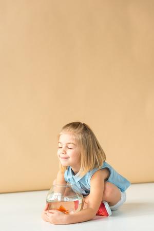 süßes Kind, das mit gekreuzten Beinen sitzt und Goldfischglas auf beigem Hintergrund hält