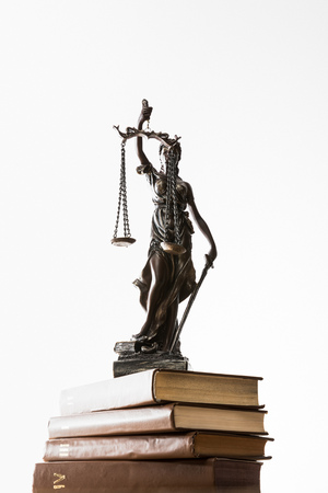 low angle view of bronze figurine with scales of justice on pile of brown books isolated on white