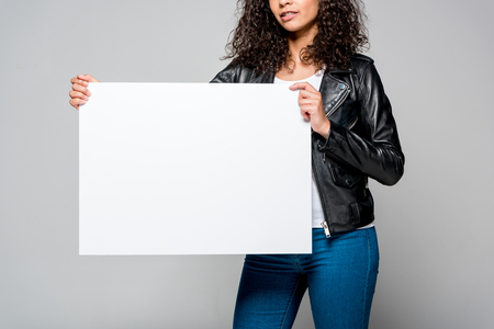 cropped view of african american young woman holding blank placard isolated on grey