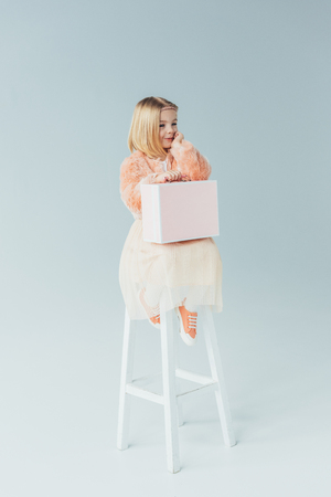 dreamy kid in faux fur coat and skirt sitting on highchair and holding pink case Stock Photo