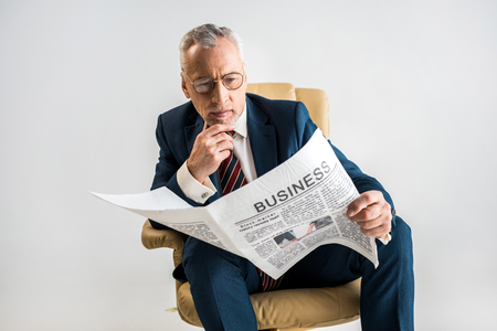mature businessman sitting in armchair and reading business newspaper isolated on grey