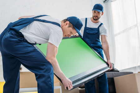 two handsome movers in uniform transporting tv with green screen in apartment