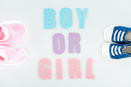 top view of booties and sneakers, boy or girl lettering isolated on white