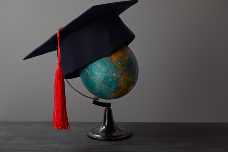 Academic cap with red tassel on globe on dark surface