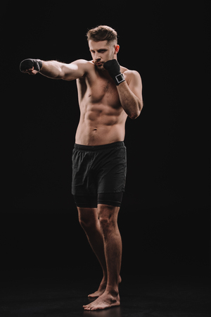 strong barefoot muscular mma fighter in bandages and shorts doing punch on black