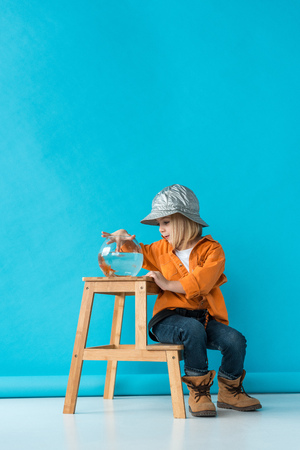 kid in jeans and orange shirt sitting on stairs and playing with goldfish Foto de archivo - 120196702
