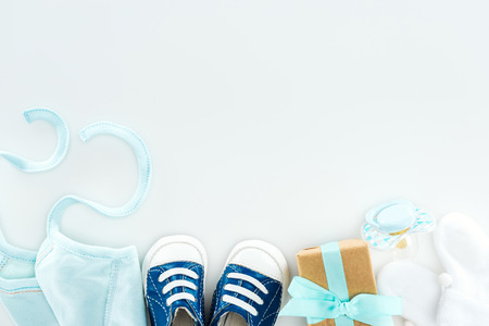 top view of booties and sneakers, pacifier, gift box and bonnet on white background