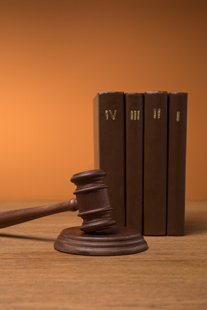 volumes of brown books in leather covers and gavel on wooden table Imagens