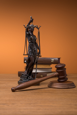 bronze statuette with scales of justice, gavel and books on wooden table on orange background Stock Photo