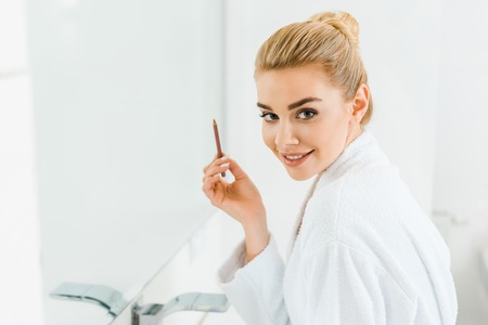 beautiful and smiling woman in white bathrobe holding lip liner and looking at camera 版權商用圖片
