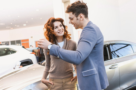 happy man in glasses looking at cheerful curly woman standing with hands in pockets in car showroom Stock Photo