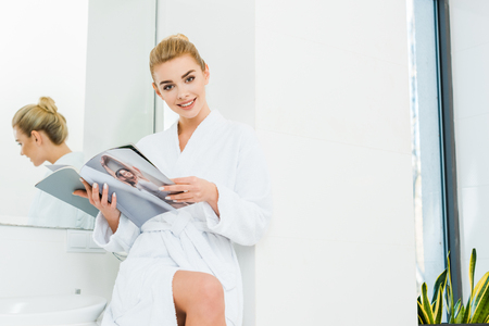 beautiful and smiling woman in white bathrobe holding magazine and looking at camera