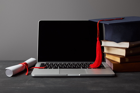 Laptop with blank screen, diploma, books and academic cap with red tassel isolated on grey