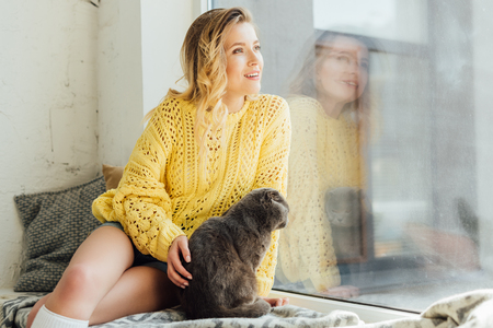 beautiful smiling young woman stroking scottish fold cat while sitting on window sill with copy space