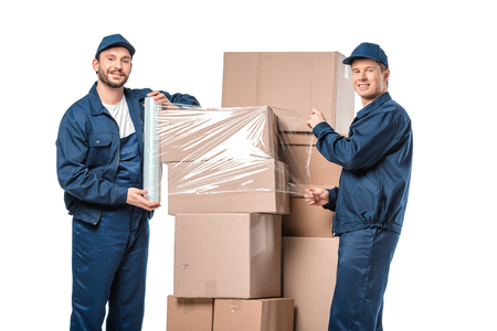 two movers looking at camera and wrapping cardboard boxes with roll of stretch film isolated on white