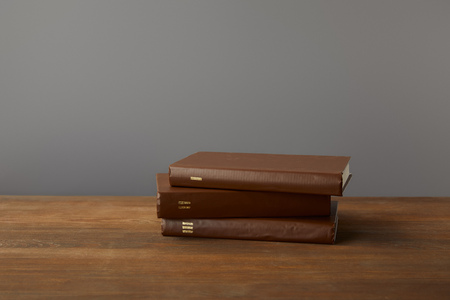 Three brown books on textured wooden surface on grey