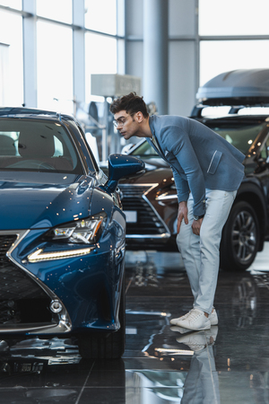 handsome stylish man in glasses standing near auto in car showroom