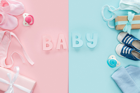 top view of pacifiers, gifts, bonnets, hat, booties,sneakers and baby lettering