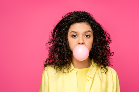 attractive curly african american woman blowing bubble gum isolated on crimson