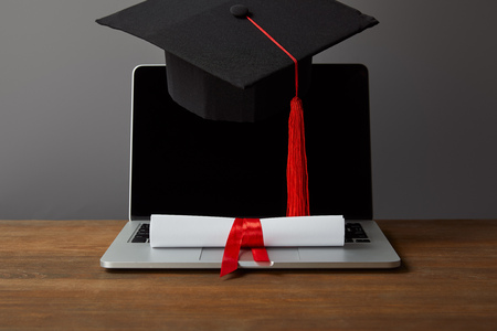 Laptop with blank screen, diploma and academic cap with red tassel on grey