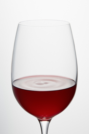 Wine glass with burgundy red wine isolated on white