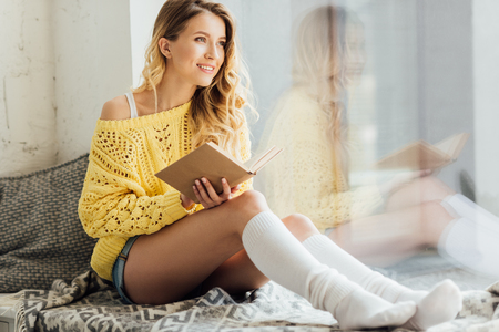 beautiful smiling young woman holding book while sitting on window sill with copy space