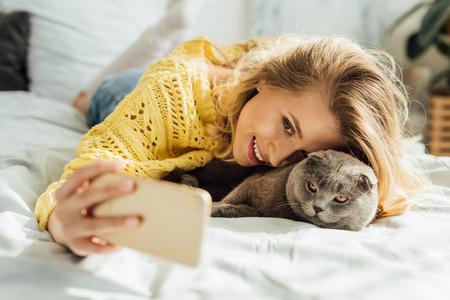 schöne lächelnde junge frau, die selfie auf dem smartphone macht, während sie mit schottischer faltenkatze im bett liegt Standard-Bild