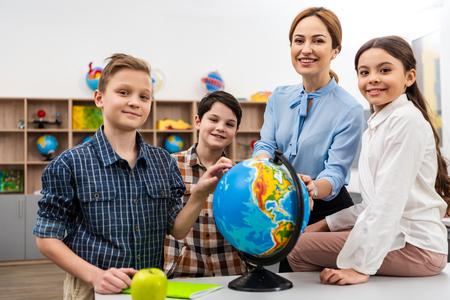 Profesor y alumnos tocando el globo con una sonrisa mientras estudian geografía en el aula Foto de archivo