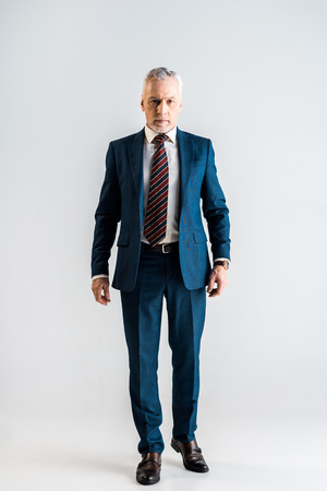 serious middle aged businessman in suit standing on grey Reklamní fotografie