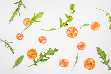 sliced red tomatoes and  green arugula leaves on grey background