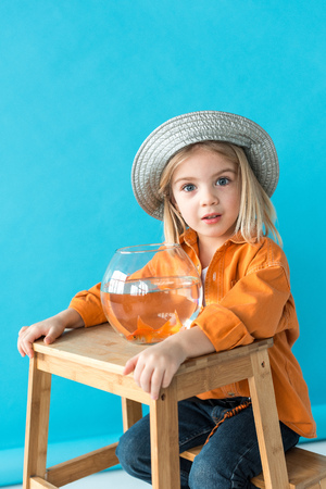 kid in silver hat and orange shirt sitting on stairs with fishbowl on blue background Standard-Bild