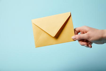 Ausgeschnittene Ansicht einer Frau, die einen hellen und gelben Umschlag auf blauem Hintergrund hält