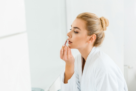 beautiful and blonde woman in white bathrobe applying lip liner in bathroom Stock Photo