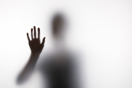 Blurry silhouette of person touching glass with hand Stock fotó
